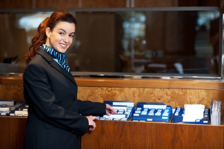 hotel worker: Front office female assistant checking customer records at work. Looking at camera Stock Photo