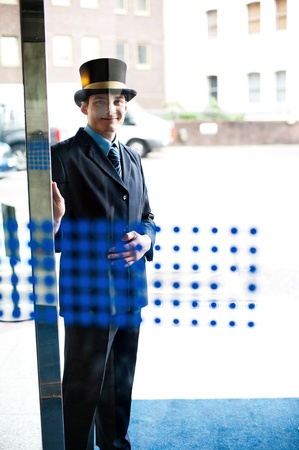 doorkeeper: Hotel doorman at your service. Buildings and cars in the background