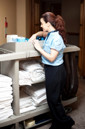 Pretty housekeeping executive busy working. Checking toiletries, towels and bed sheets arranged in a cart photo