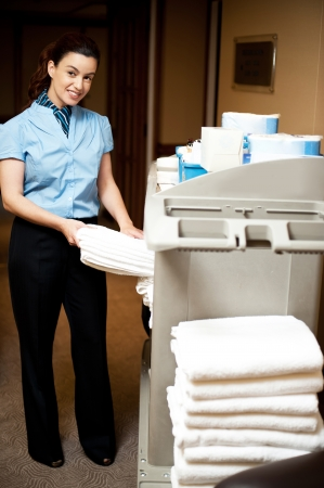 hotel hallway: Housekeeping in charge pulling out the bath towel from the cart to deliver it to rooms
