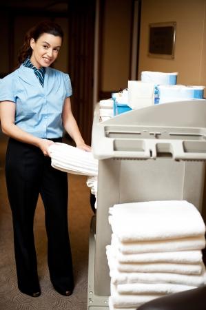 housekeeping: Servicio de limpieza a cargo tirando la toalla de ba�o de la carreta para entregarlo a las habitaciones Foto de archivo