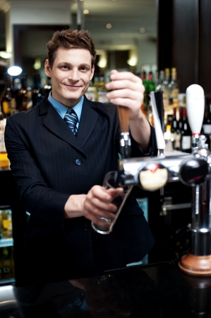 Handsome mixologist putting ice into tall glass. Bar decorated with bottles in the background photo