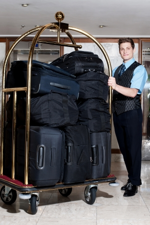 bellhop: Conserje masculino hermoso que presenta con un mont�n de bolsas en el carrito de equipaje