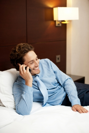 hotel room: Delighted young man communicating with his partner on the phone. Relaxed in hotel room