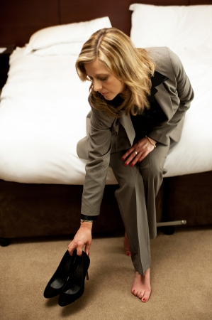 An active charming lady keeping her foot wear aside before leaning on the bed photo