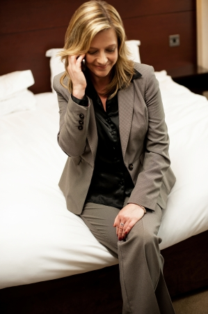 Businesswoman communicating with her husband. Very much relaxed in her hotel room photo