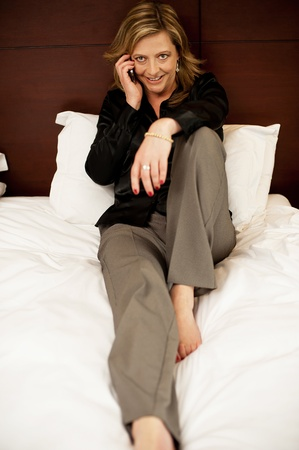 Pretty woman relaxing in bed and talking on phone while looking at camera photo