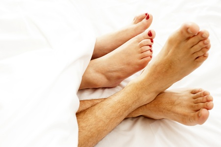 Closeup of bare feet of love couple, making out. Covered with white sheets photo