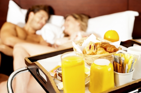 sexual couple: Lets wake up with healthy breakfast sweetheart. Couple romancing in bed