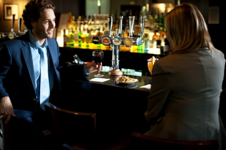 cuisine entertainment: Attractive couple refreshing themselves at the bar. Enjoying drinks Stock Photo
