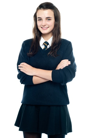 school uniform girl: Pretty smiling teenager looking at you confidently. Arms folded
