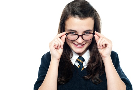 closer: Schoolgirl adjusting her spectacles. Let me take a closer look at you Stock Photo