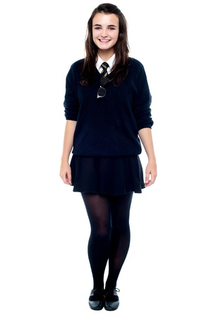 hair tie: Full length portrait of pretty girl in school uniform isolated against white background