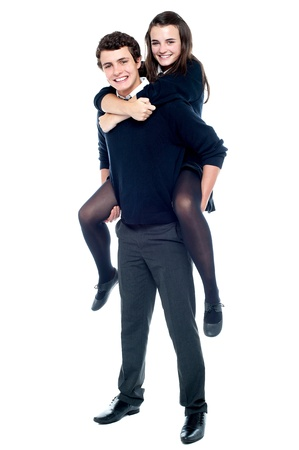 Schoolboy carrying girl on his back. Full length shot Stock Photo - 15710757