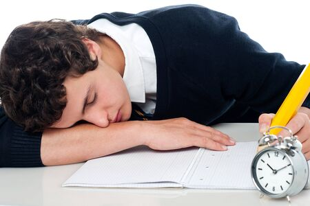 Teenager dozing off while writing his test. Fast asleep Stock Photo - 15710780