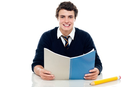 studious: Studious boy preparing for half yearly exams. Holding his notebook and reading Stock Photo
