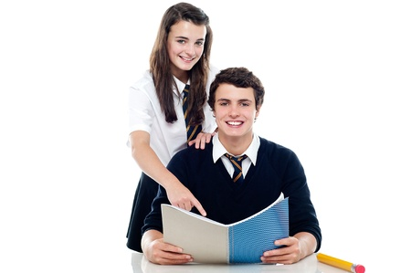 Girl pointing out the answer to her classmate. Cheerfully posing in front of camera