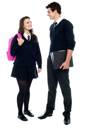 Casual shot of students looking at eachother and engaged in a jovial discussion isolated against white background photo