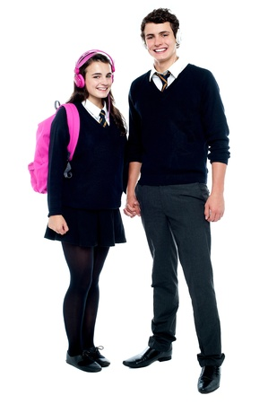 School friends with headphones on enjoying music  Holding hands, full length portrait photo