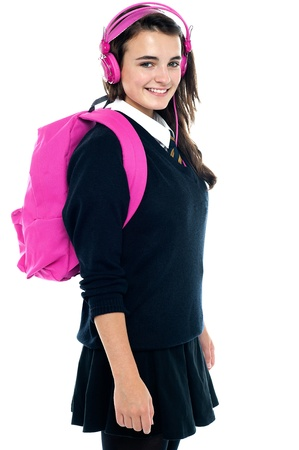 Schoolgirl with pink backpack and matching headphones enjoying music photo