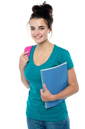 College student carrying backpack and spiral notebook isolated against white background Stock Photo - 15714994