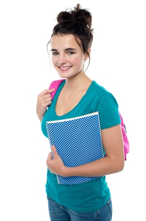 to attend: Pretty teenager ready to attend college. Carrying backpack on her shoulders