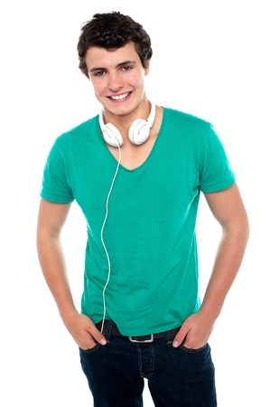 casually: Cool trendy teenager boy with headphones around his neck. Posing casually and smartly