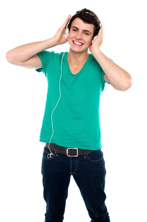 Cheerful guy enjoying loud music holding them tightly to ears photo