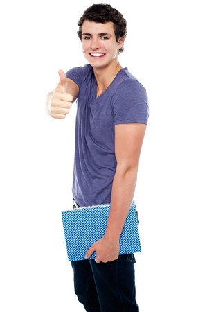 posing  agree: Fashionable youth with a notebook in hand showing thumbs up sign to the camera