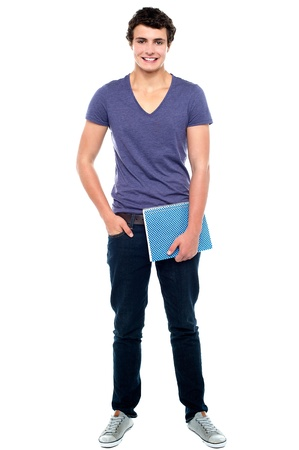 Stylish college student posing with notebook in one hand and other hand in  pocket Stock Photo - 15714947