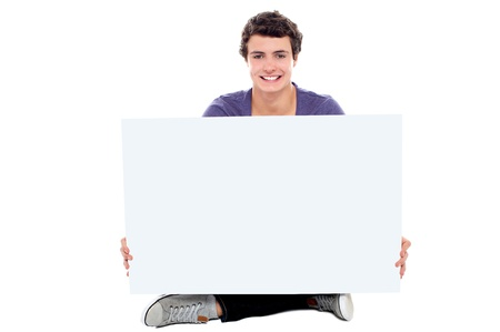 Teenager showing blank white billboard to camera. Get your business ad here Stock Photo - 15714925