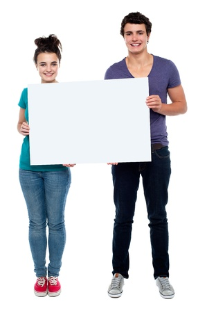 promoting: Full length portrait teen couple posing with blankbill board