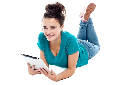 causal: Causal teenager lying on floor holding new tablet pc. Looking at camera Stock Photo