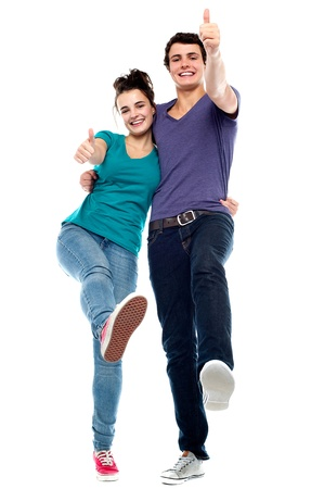 yup: Teen love couple enjoying themselves, gesturing thumbs up. All against white background