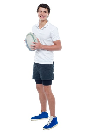 Full length portrait of a rugby player holding ball. All against white background photo