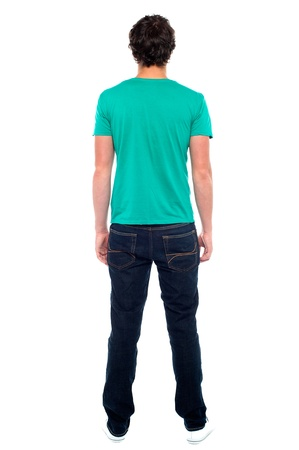 Rear view of teen guy in casuals. Full length portrait photo