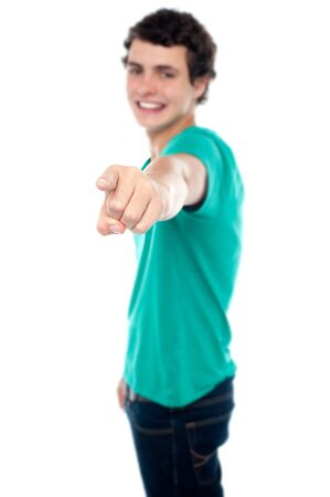 Casual teen guy pointing at you isolated against white Stock Photo - 15714926