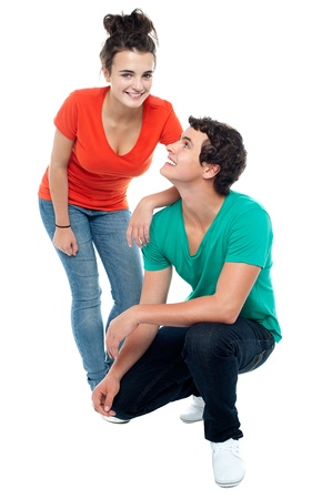 Adorable young guy squatting on floor and looking at his girlfriend