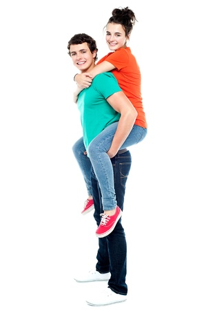 Portrait of loving couple enjoying together while piggyback ride photo