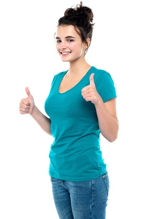 yup: Gorgeous looking casual teenager showing double thumbs up to camera isolated against white background Stock Photo