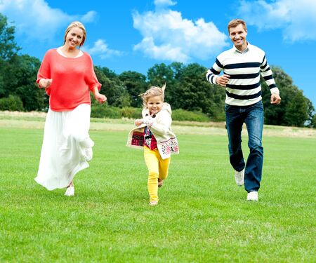 Young couple racing with their cute little daughter outdoors. Day time photo