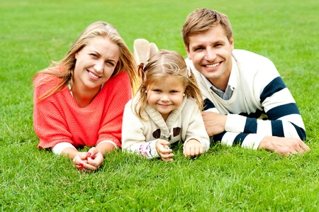 Portrait of a happy family of three lying in the lawn, having fun photo
