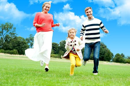 Young couple racing with their cute little daughter. Running in park photo