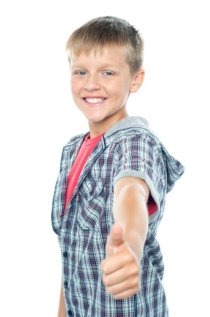 posing  agree: Handsome young boy gesturing thumbs up sign to camera isolated over white Stock Photo