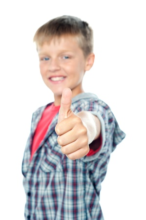 posing  agree: An adorable young caucasian boy showing thumbs up sign to the camera