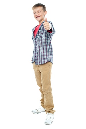 posing  agree: Full length portrait of smartly dressed young kid showing thumbs up gesture to camera Stock Photo