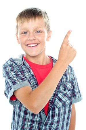 Young boy posing on white background. Pointing finger towards copyspace area photo