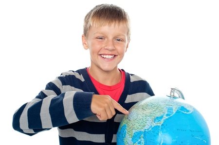 Cute little boy pointing out a continent on the globe. Isolated on white photo