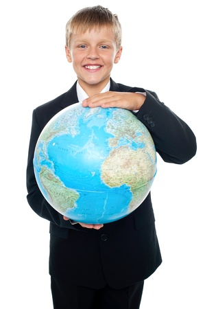 Cheerful boy in suit holding globe with both hands. Isolated on white photo