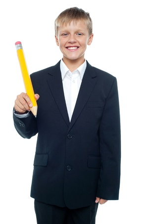 formals: Cheerful young boy holding giant sized yellow pencil dressed in formals Stock Photo